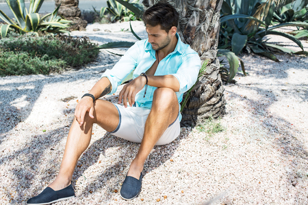 Fashion male model sitting under the palm tree and thinking