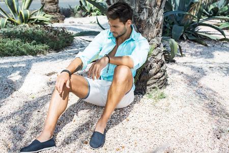 modelos hombres: Modelo de manera masculino que se sienta debajo de la palmera y el pensamiento