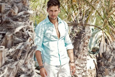 英俊的模型在棕榈树下
