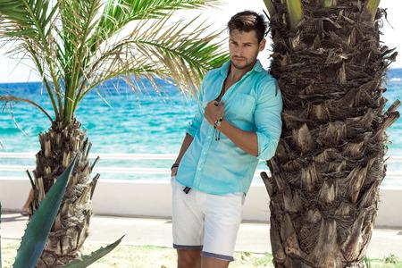 Modello bello in camicia turchese in posa in uno scenario estivo
