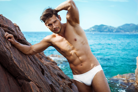 naked: Sexy man in underwear posing on sea scenery Stock Photo