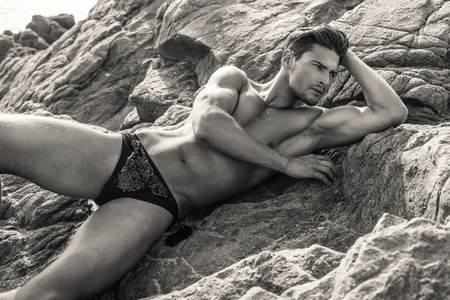 Sexy Male Model In Underwear Lying And Posing On The Rocks Stock Photo