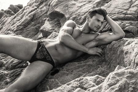 Sexy modelo masculino en ropa interior acostada Y presenta en las rocas