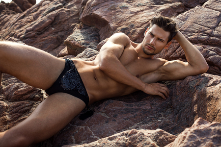 naked male body: Handsome man in underwear lying on the rocks Stock Photo