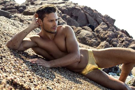 nudo maschile: Uomo sexy in biancheria intima posa sulla spiaggia Archivio Fotografico