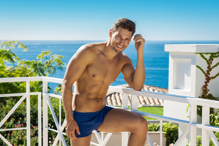 nude male body: Handsome smiling man wearing swimming trunks in sea scenery