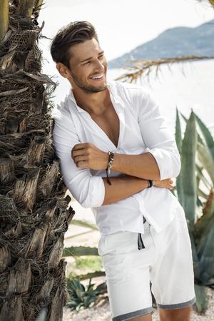 여름 풍경에서 흰 셔츠를 입고 명랑 웃는 젊은 남성 모델