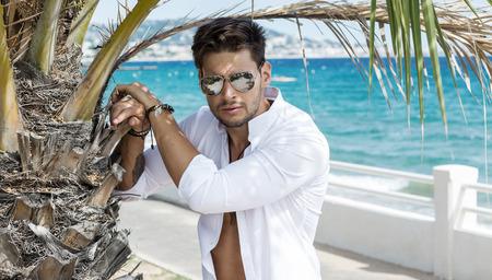Portrait of handsome model wearing aviator sunglasses in summer scenery