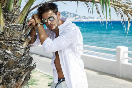 blue shirt: Sexy model wearing white shirt in aviator sunglasses Stock Photo