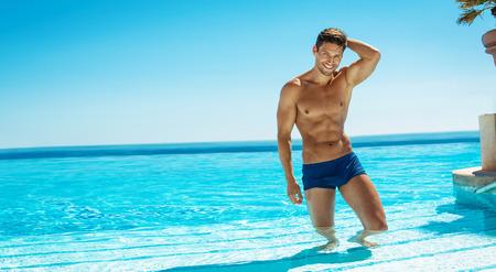desnudo masculino: Foto del verano del hombre sonriente muscular en la piscina de natación Foto de archivo