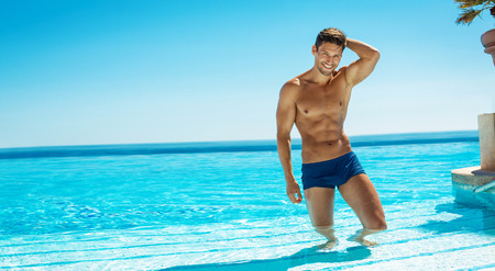 naked male body: Summer photo of muscular smiling man in swiming pool