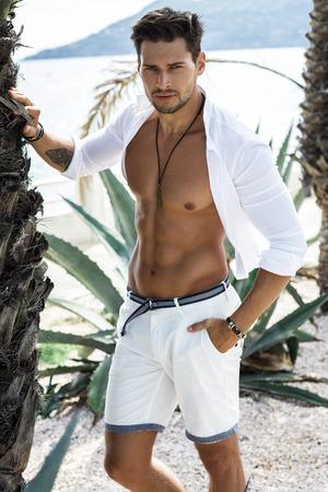nudo maschile: Handsome modello maschile che indossa camicia bianca in posa in uno scenario estate