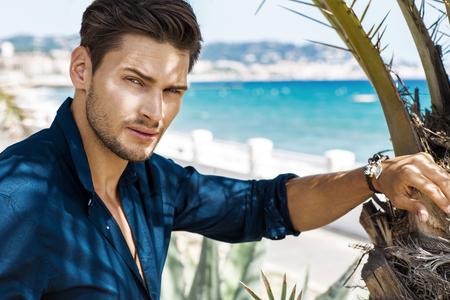 blue shirt: Portrait of handsome model with sea view