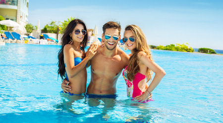 Group Of Smiling Friends Having Fun In Swimming Pool And Wearing Sunglasses Stock Photo