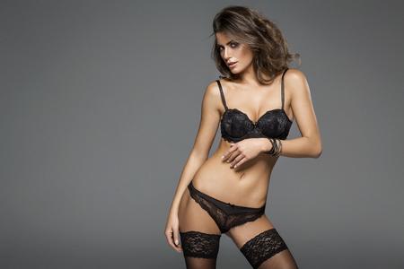 mujeres eroticas: Sexy mujer morena atractiva posando en ropa interior de moda en estudio Foto de archivo