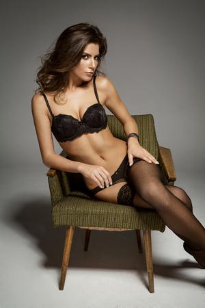 femmes nues sexy: brunette modèle de beauté assis sur une chaise en lingerie Banque d'images