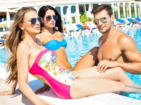 nadar: Retrato de jóvenes amigos en la piscina y con gafas de sol en tiempo de verano