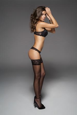 mujeres eroticas: Mujer atractiva con las piernas largas presenta en ropa interior de moda en el estudio. pantimedias desgaste de mujer
