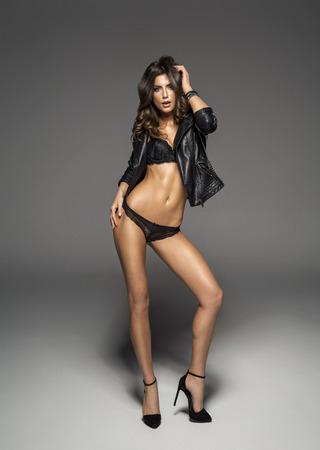 femme noire nue: modèle féminin en lingerie sexy et veste en cuir