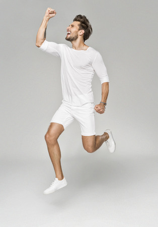 euphoria: Handsome man in white clothes jumping in euphoria Stock Photo