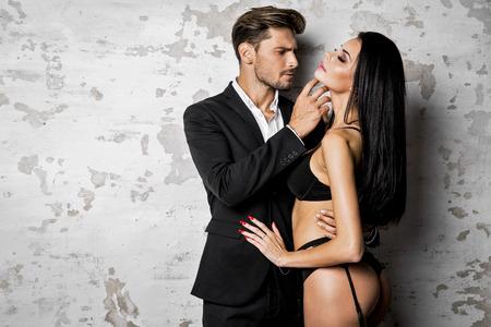 Uomo bello in vestito nero, toccando donna sexy in lingerie