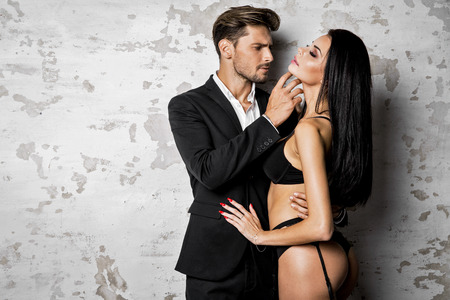 Knappe man in zwart pak aanraken van sexy vrouw in lingerie