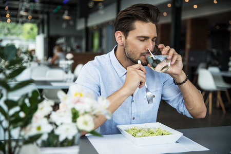 Handsome man drinking water and enjoy his meal