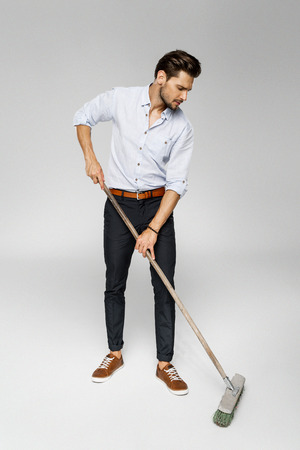 Handsome man with broom