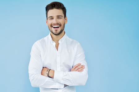 hombre guapo sonriente atractiva con los brazos cruzados Foto de archivo