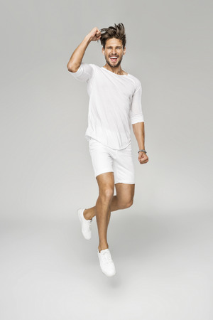 Handsome man in white clothes jumping