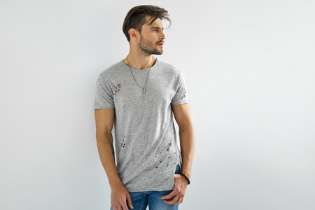 Handsome man in grey t-shirt posing on white background
