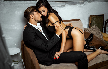 undressed: Undressed woman sitting on a couch kissing and touching handsome man Stock Photo