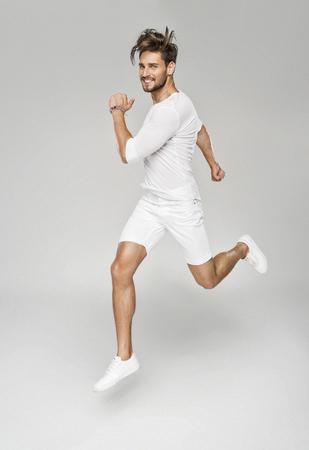 Knappe man in witte kleren springen