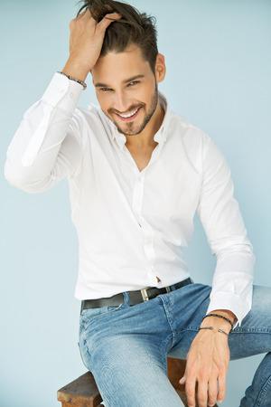 Portret van glimlachende man met hand in zijn haar Stockfoto - 62133261