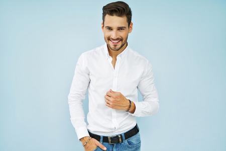 Enthousiaste jeune modèle mâle souriant en chemise blanche