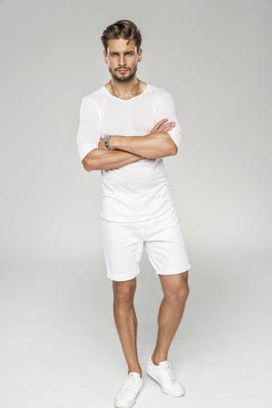 Modelo masculino hermoso con los brazos cruzados llevar ropa blanca Foto de archivo