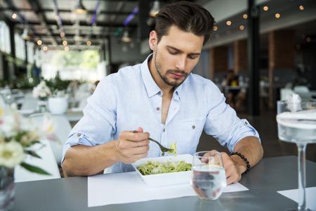 Handsome man eating pasta