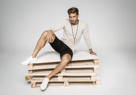 Sexy man sitting on pallets and posing Zdjęcie Seryjne