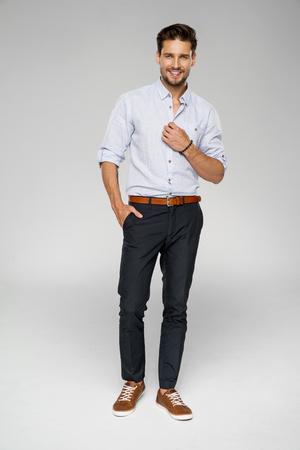 ハンサムな男は青いシャツとスタジオでポーズを着用します。