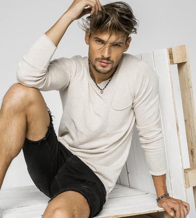 Portret van knappe man met de hand in zijn haar en zittend op pallets