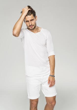 Modelo masculino hermoso que toca su pelo