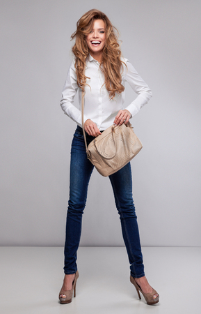 Beautiful happy woman holding a bag photo