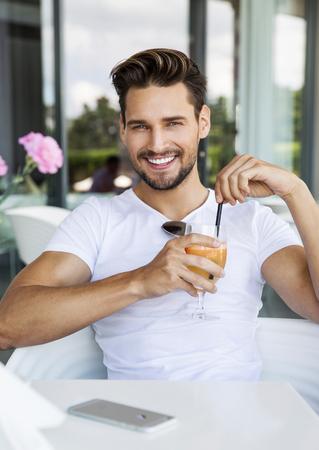 ornage: Handsome man drinking ornage juice