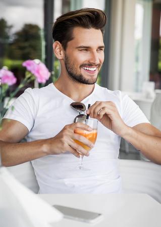 Handsome man drinking ornage juice