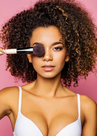 Portrait of the beautiful black woman with make-up brush near attractive face Stock Photo