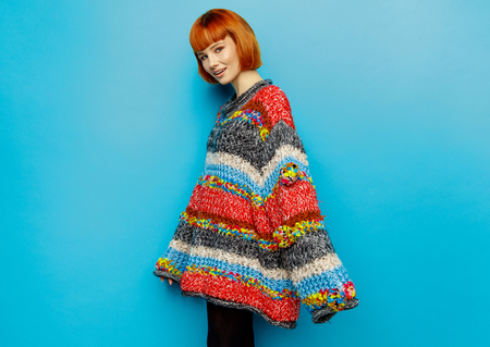 Colorful photo of young female model wear oversize sweater isolated on blue background