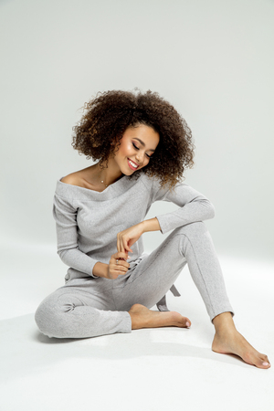 Beautiful black woman relaxing and smiling, isolated on grey background