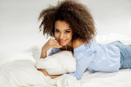 Beautiful african american girl with an afro hairstyle lying in bed and smiling Banque d'images
