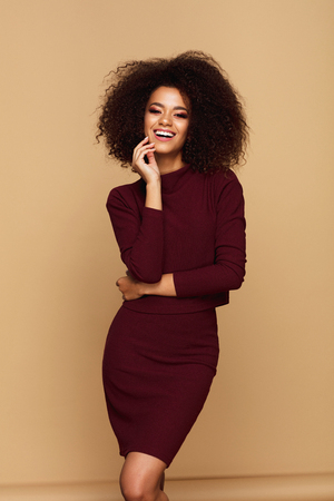Beautiful african american woman with afro isolated on studio background with copy space Imagens
