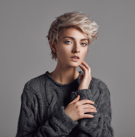 Fashion portrait of young woman with blond short hair isoalted on gray background Stock Photo